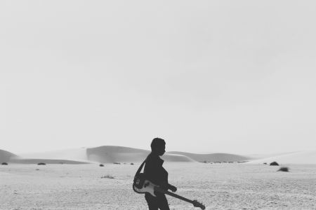 Man with guitar in the desert