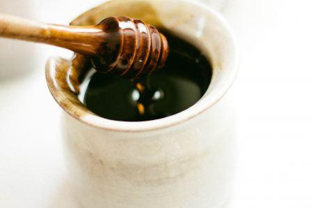Honey dipper over a honey pot