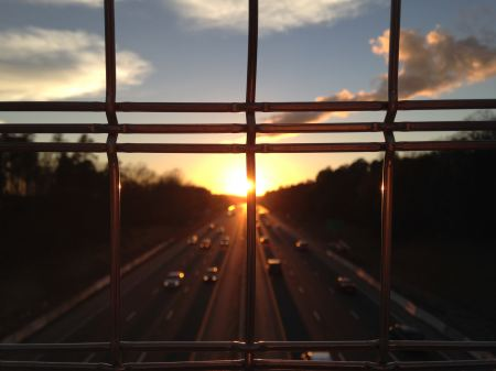 Sunset on the highway seen through the bars