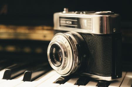 Vintage camera sitting on piano keys