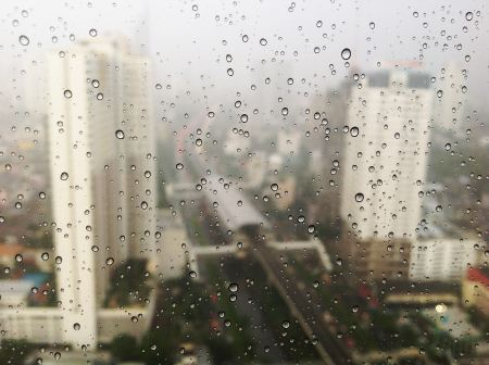 City view through raindrops of the window