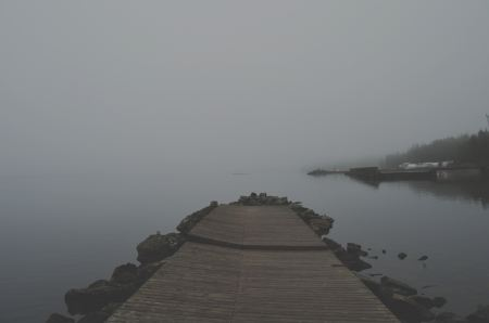 Old pier on a lake in the fog