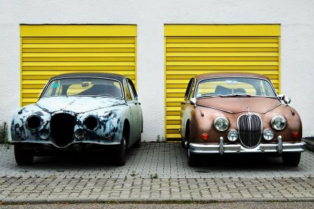 Two vintage cars in front of garages